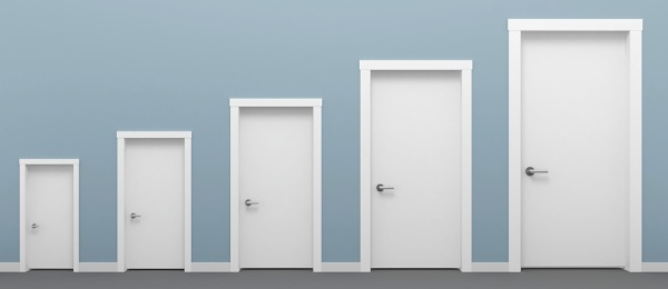 A row of plain doors on a plain wall, growing in size from left to right.