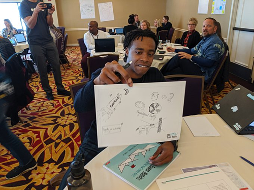 An Education Elements Teammate holds up a sheet of paper with graphic illustrations for idea visualization