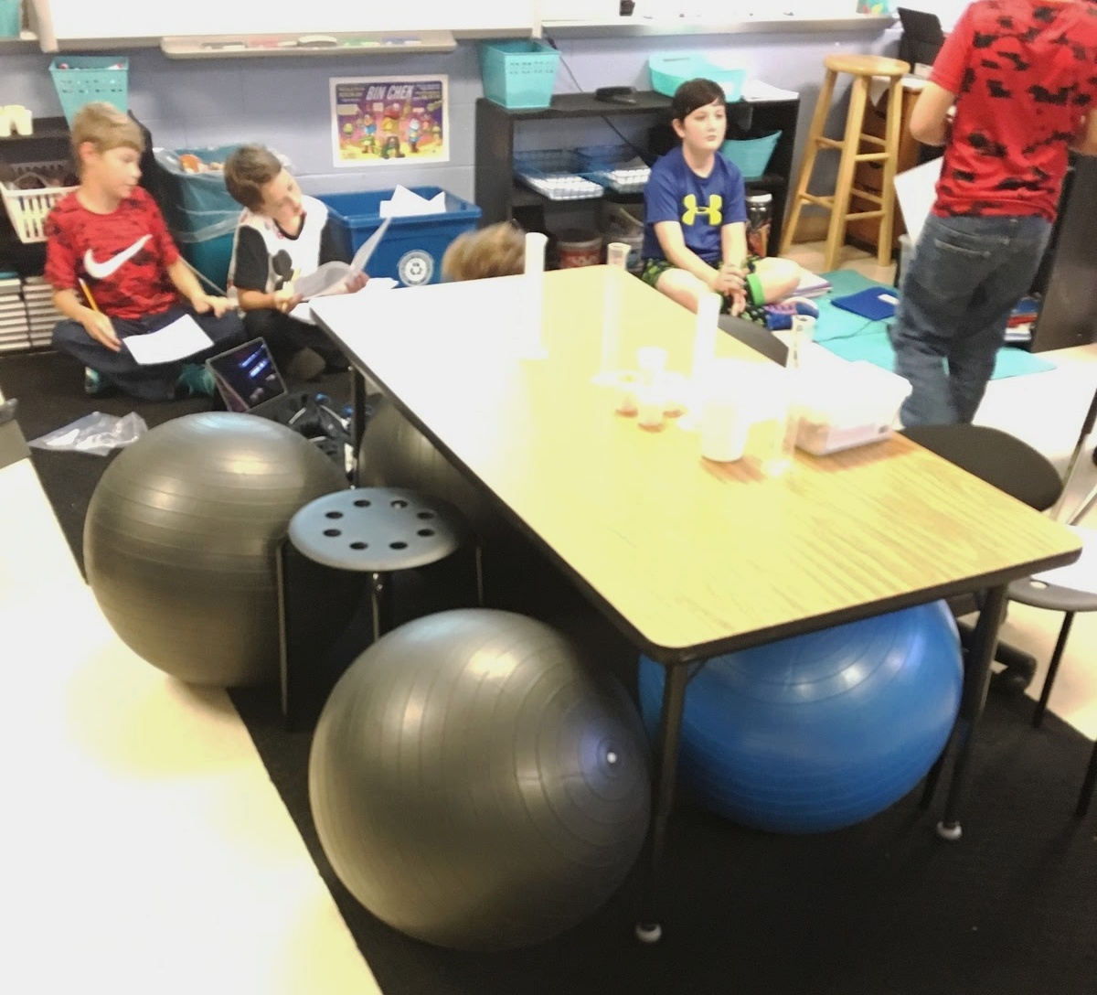 An image of a communal desk in a classroom with exercise balls for seats.