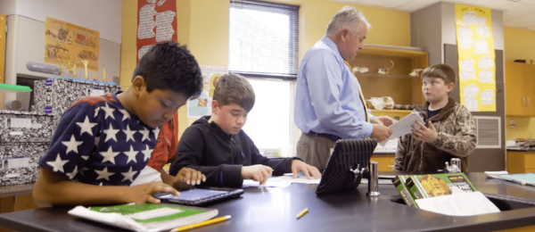 Students working independently in a classroom, as an instructor collects assignments.