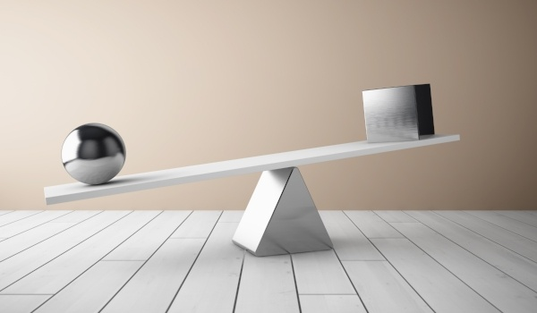 A sphere and cube balancing on a scale.