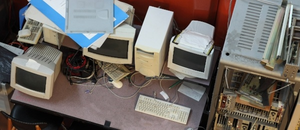 Old computer monitors, keyboards, mouses, motherboards - and other computer parts - in a junkyard.