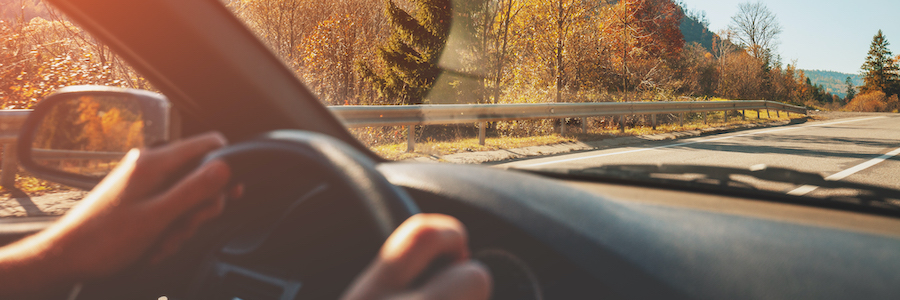 Person's hands on steering wheel of car, driving down a highway with mountains and trees in the background
